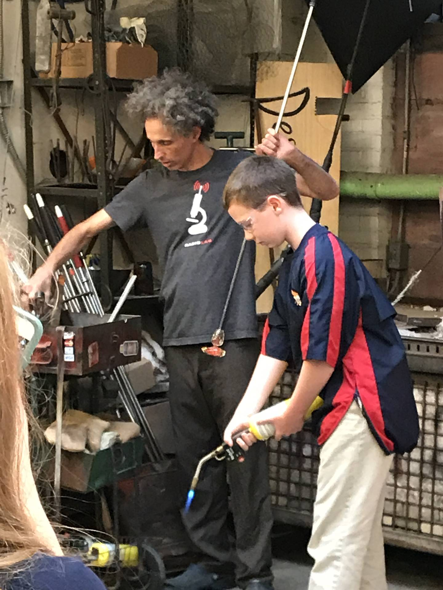 Grade 7 student participates in a glass blowing demonstration